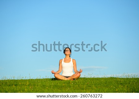 Young woman doing yoga relaxing and breathing exercise outdoor. Relax and tranquility at green grass field towards blue clear sky. - stock photo