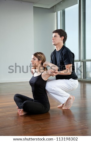 Young woman doing yoga with help from male instructor at gym