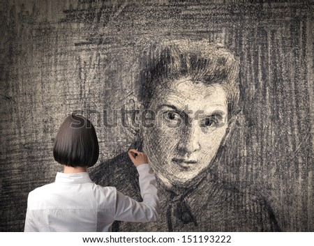 young woman draws a portrait - stock photo