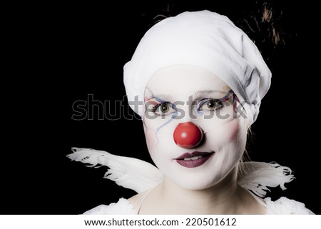 Young woman dressed as a happy clown, with angels wings and white underwear on her head - stock photo