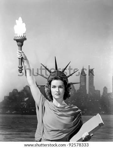 Young woman dressed as the Statue Of Liberty with skyscrapers in the background - stock photo