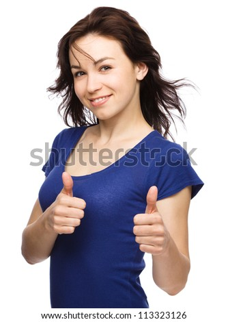 Young woman dressed in blue dress is showing thumb up gesture using both hands, isolated over white - stock photo