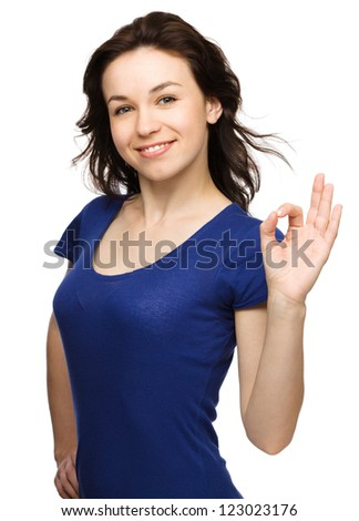Young woman dressed in blue is showing OK sign, isolated over white