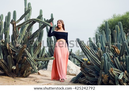 Young woman dressed in hippie clothes standing near big cactus - stock photo