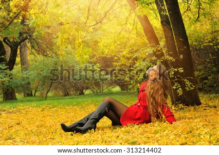 Young woman dressed in red coat relaxing on a foliage in autumn park.