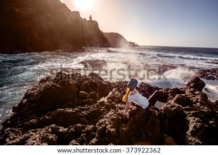 Young woman dressed in white enjoying sunset sitting on the rocky coast