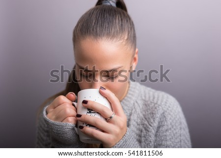 Young woman drink coffee or tea. isolated gray.