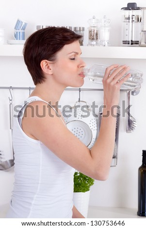 young woman drinking a bottle of refreshing water in her kitchen