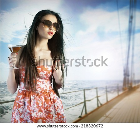 Young woman drinking a cocktail on the deck - stock photo