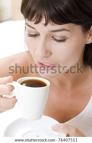 young woman drinking a coffee sitting on her bed - stock photo
