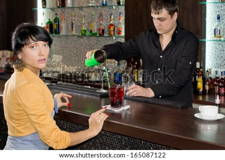 Young woman drinking at a bar turning to look at the camera in surprise as the barman mixes cocktails behind the counter