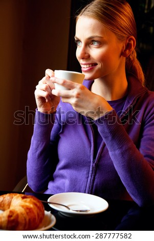 young woman drinking cappuccino at breakfast - stock photo