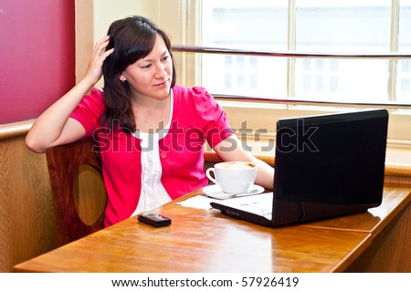 young woman drinking cappuccino using her laptop in a cafe - stock photo