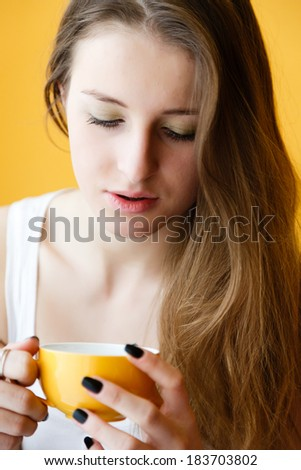 Young woman drinking coffee and dreaming - stock photo