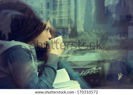 Young woman drinking coffee and reading book sitting indoor in urban cafe. Cafe city lifestyle. Casual portrait of teenager girl. Toned. - stock photo
