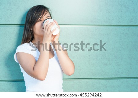 Young woman drinking coffee from takeaway mug outside on green wall with copy advertising area - stock photo