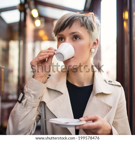 Young woman drinking coffee in a cafe in Paris, France. Shallow depth of field.