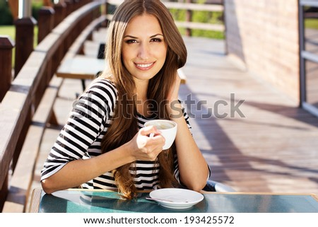 Young woman drinking coffee in a cafe outdoors - stock photo