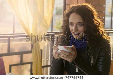 Young woman drinking coffee in cafe, sunny autumn weather