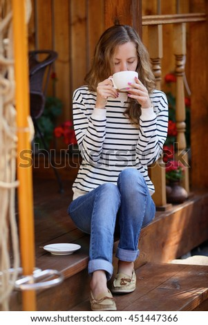 Young woman drinking coffee or tea sitting on the wooden porch - stock photo