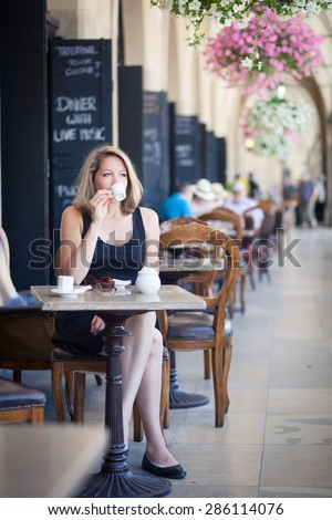 Young woman drinking coffee outdoors in a European style cafe - stock photo