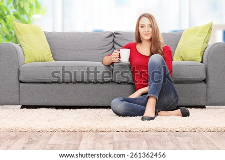 Young woman drinking coffee seated by a sofa at home  - stock photo