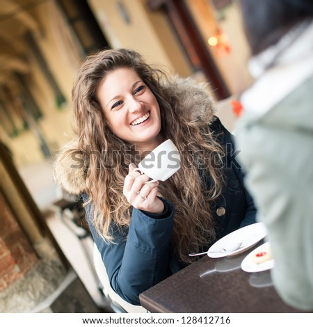 Young woman drinking coffee with friend in a cafe outdoors. Shallow depth of field. - stock photo