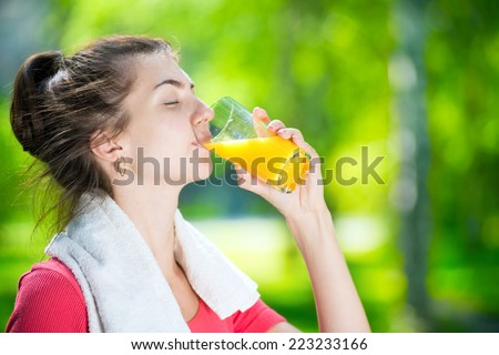 Young woman drinking fresh orange juice after sport fitness exercise at green summer park - stock photo