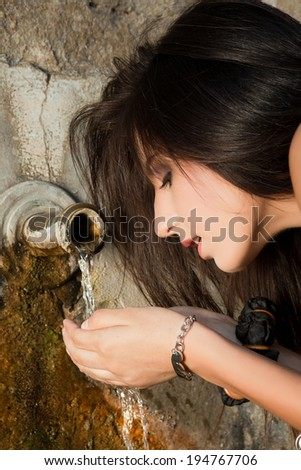Young woman drinking fresh water from a well - stock photo