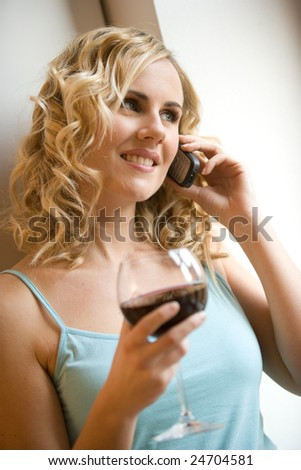 young woman drinking from a glass of red wine - stock photo