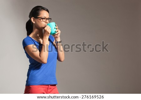 Young woman drinking from a mug of tea - stock photo