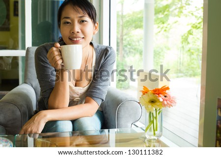 Young woman drinking  hot coffee in sidewalk cafe - stock photo