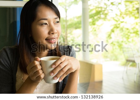 Young woman drinking  hot coffee in  sidewalk cafe
