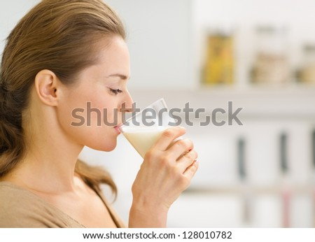 Young woman drinking milk in kitchen - stock photo