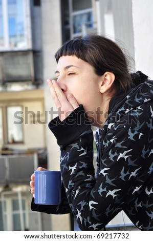 Young woman drinking morning coffee on the balcony - stock photo
