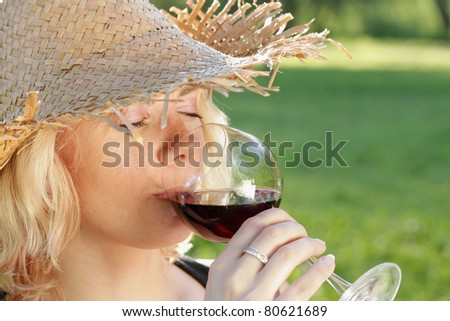 Young woman drinking red wine, outdoor portrait.