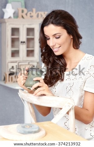 Young woman drinking tea at retro home, smiling, looking down. - stock photo