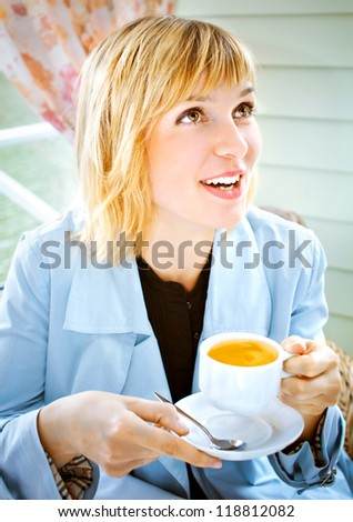 Young woman drinking tea  in the cafe open air - stock photo