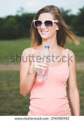 Young woman drinking water after exercise - stock photo