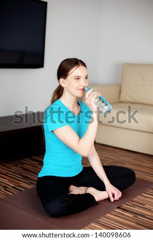 Young woman drinking water after joga exercises in living room.
