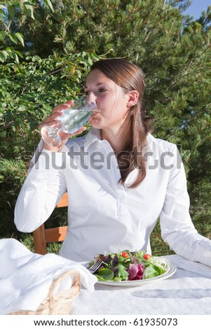 Young woman drinking water and eating a healthy salad outdoors on a restaurant patio - stock photo