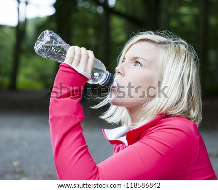 Young woman drinking water and relaxing after training - stock photo
