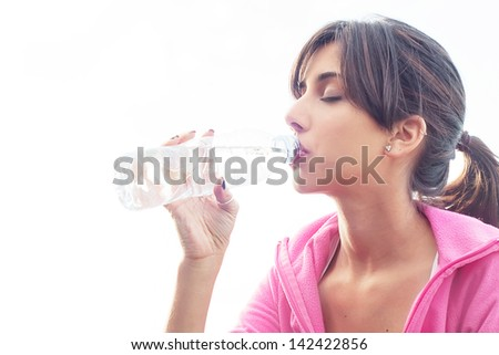 Young woman drinking water with closed eyes to recover from exercising