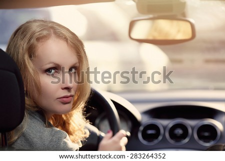 Young woman driver sitting in car - stock photo