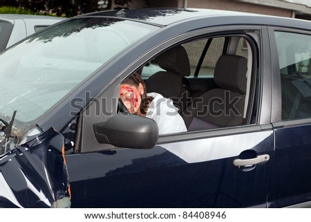 Young woman driver with bleeding face after car accident - stock photo