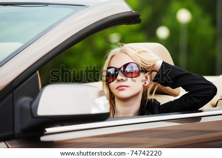 Young woman driving a convertible - stock photo