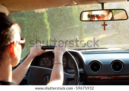 Young woman driving an old car. Selective focus on her hands and rear-view mirror. - stock photo