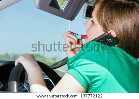 Young woman driving, applying lipstick and speaking on her smart phone - stock photo