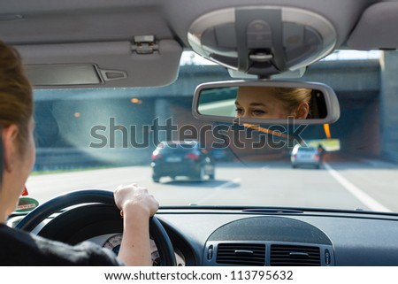Young woman driving by car on the autobahn, view from inside the auto - stock photo