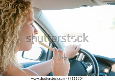 Young woman driving car and eating sweet - rear view - stock photo